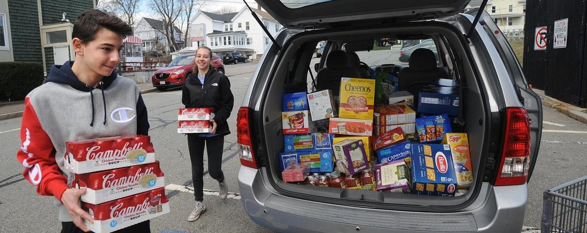 Zachary Kassoy, 16, and Jaelyn Kassoy, 19, both of Marlborough, deliver a food donation to the Marlborough Community Cupboard